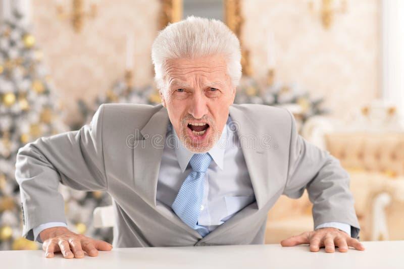 Close up portrait of angry senior businessman sitting at table. Portrait of angry senior businessman sitting at table royalty free stock images