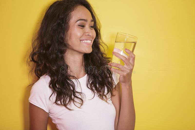 Asian girl with beautiful smile and holding a glass of water stock photo