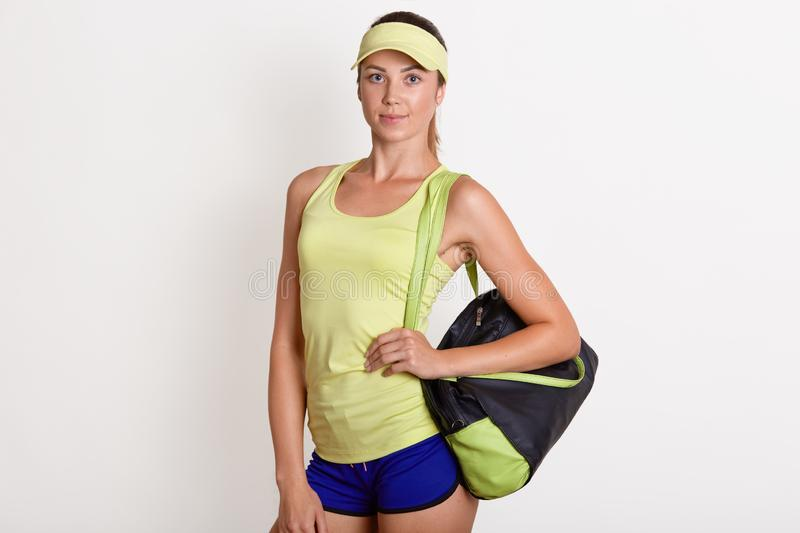Close up portrait of athletic slim sportswoman standing  over white background, holding colourful sport bag, looking royalty free stock image