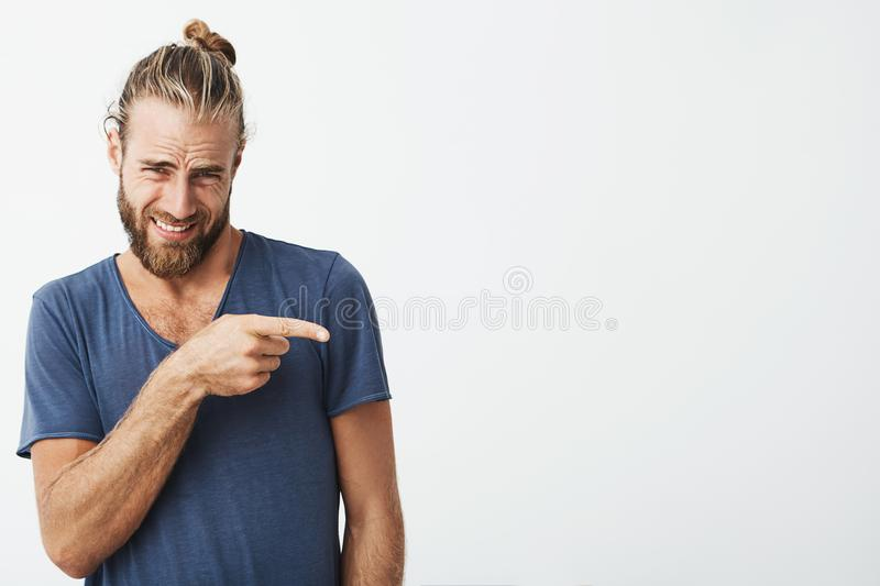 Close up portrait of attractive bearded man with trendy hairstyle pointing at white wall with disgust expression. Copy. Space stock photo