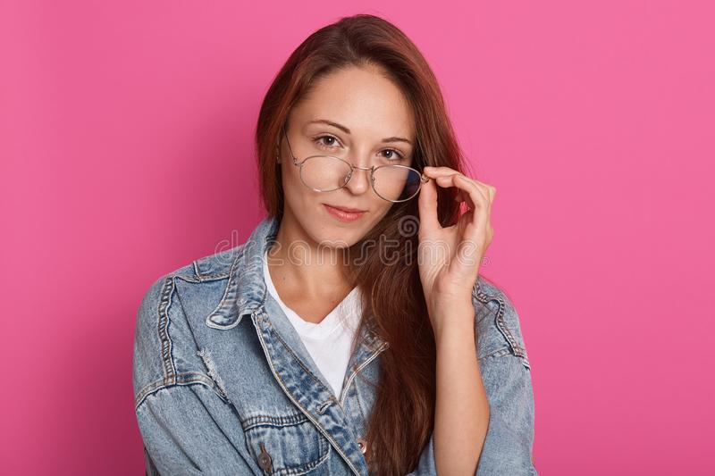 Close up portrait of attractive caucasian woman in galasses, keeps hand on her spectacles, posing isolated over pink studio stock photo