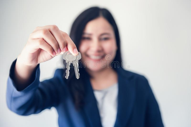 Business Woman in Uniform Suit Showing Keys for Rent Estate Housing , Beautiful of Businesswoman Broker Giving a Key to Customer,  royalty free stock photo
