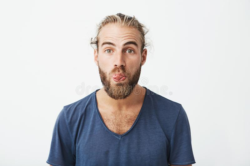 Close up portrait of attractive funny guy with stylish hairstyle and beard showing tongue and making silly expression royalty free stock images