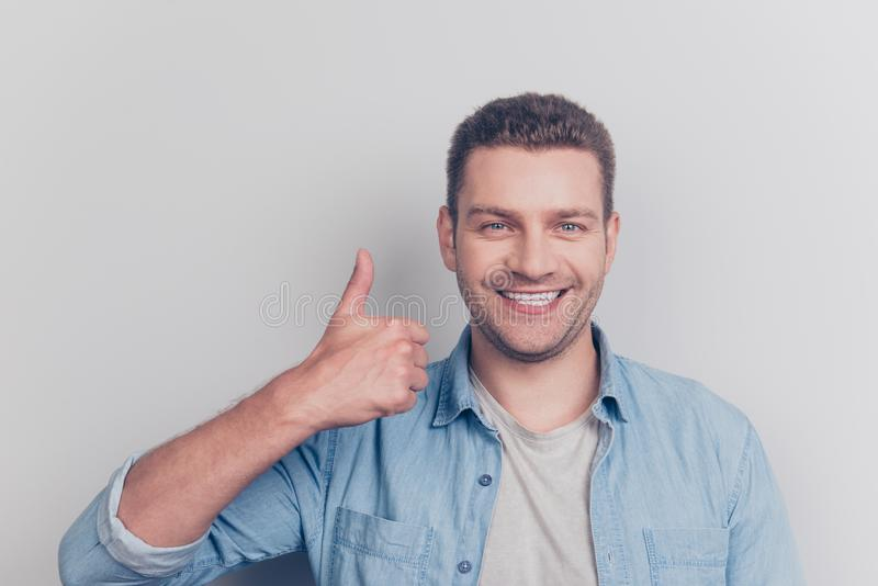Close up portrait of attractive good-looking man show thumb up s. Tand isolated on light gray background look at camera make white toothy smile stock photography