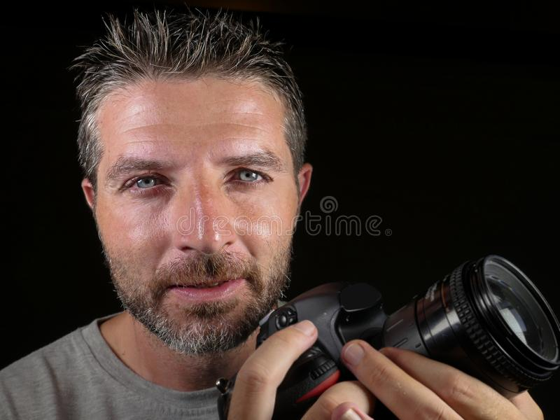 Portrait of attractive and handsome man on his 30d holding professional reflex photo camera next to his face smiling happy. Close up portrait of attractive and royalty free stock images