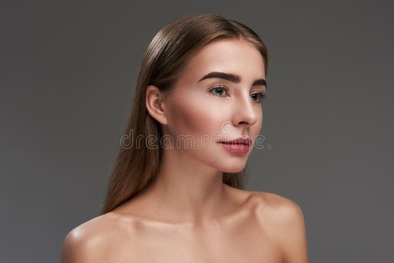 Beautiful young woman standing against gray background stock image