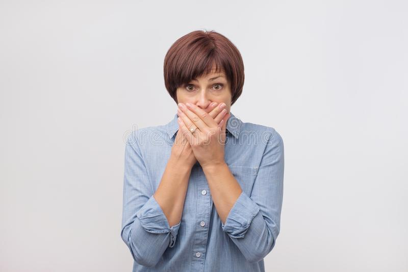 Close up portrait of attractive, mature woman in blue shirt closing her mouth with fingers. She is worried. royalty free stock photo