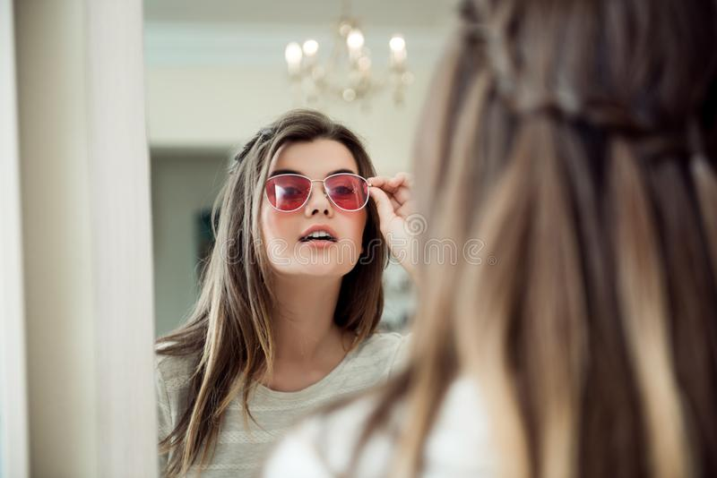 Close-up portrait of attractive modern european woman in optician store standing near mirror and trying on stylish stock images