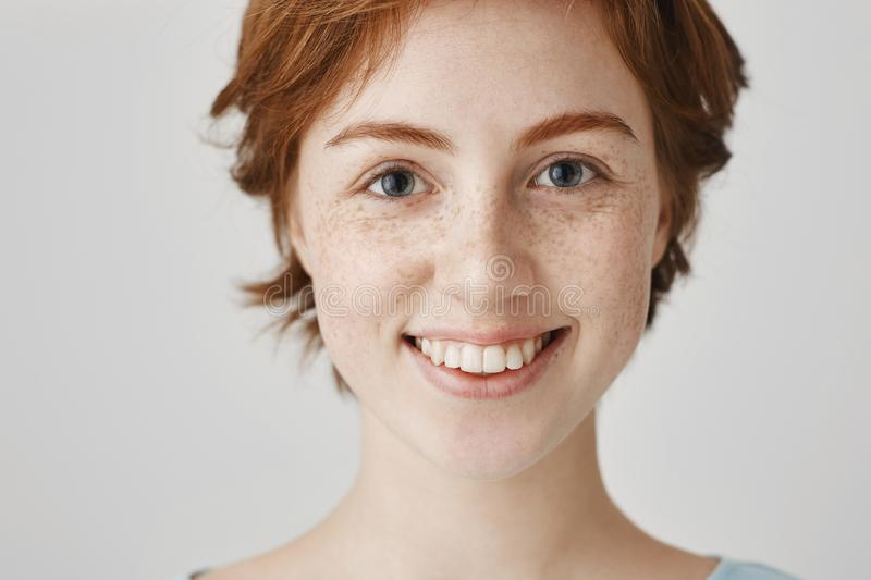 Close-up portrait of attractive redhead woman with cute freckles and clean perfect skin, smiling broadly, being in good royalty free stock images
