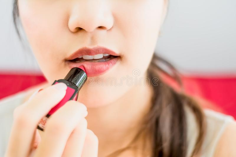 Close up portrait of attractive woman holding light pink lipstick apply to lips,Concept beauty and charm of women and makeup stock images