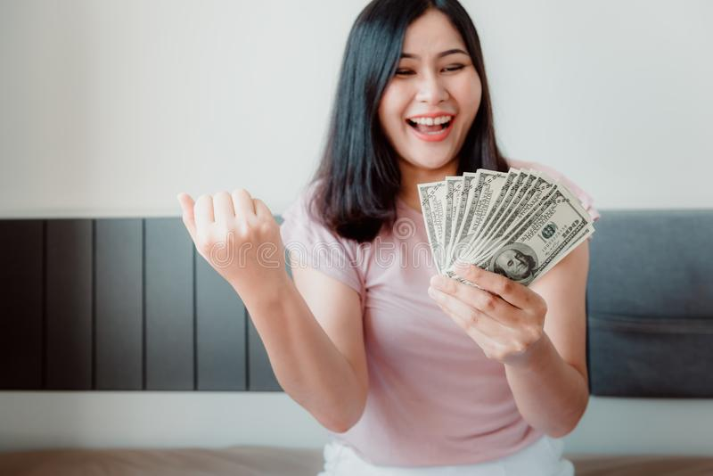 Close-Up Portrait of Attractive Woman Holding Money Cash From Savings With Happy Expression on Her Bedroom. Business Financial and royalty free stock photos