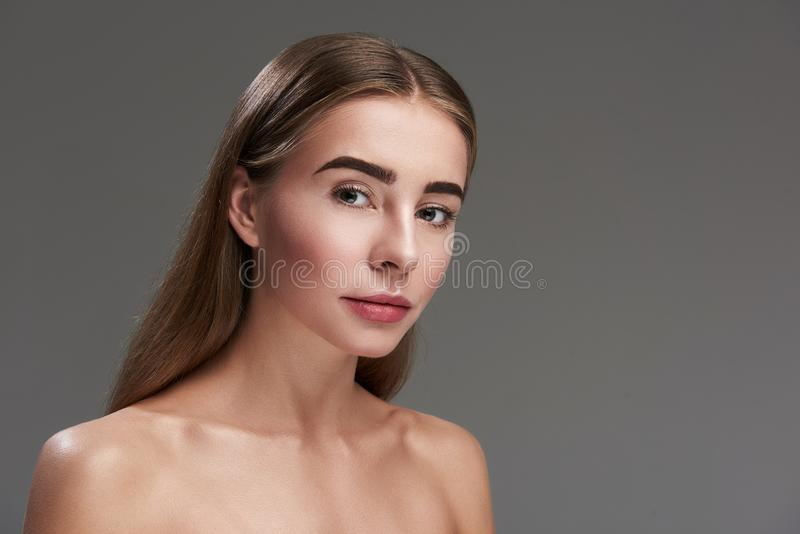 Beautiful young lady standing against gray background stock photo