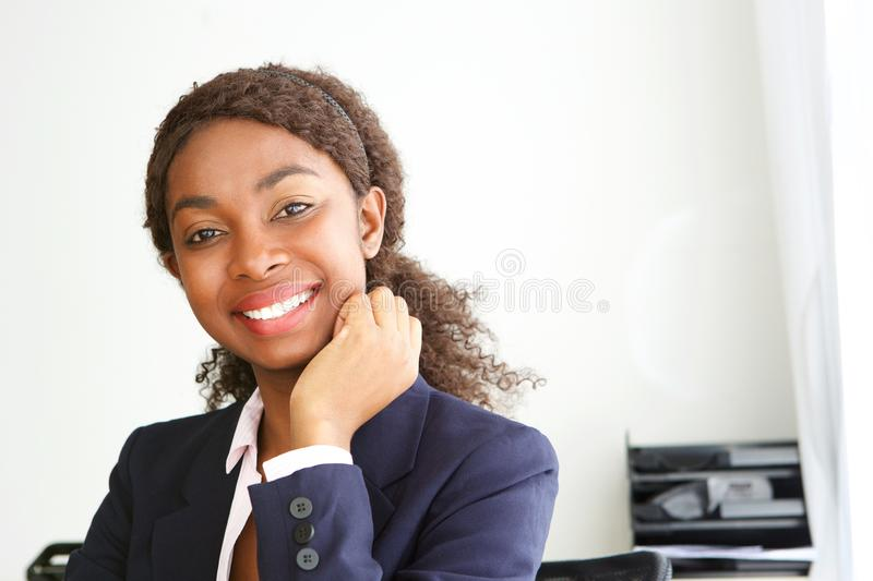 Close up attractive young african businesswoman smiling in office. Close up portrait of attractive young african businesswoman smiling in office royalty free stock photography