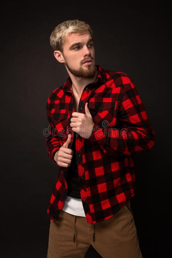 Image of attractive young bearded hipster man dressed in shirt in a cage isolated over black background. royalty free stock photography