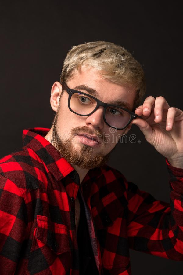 Image of attractive young bearded hipster man wearing glasses dressed in shirt in a cage isolated over black background. stock image