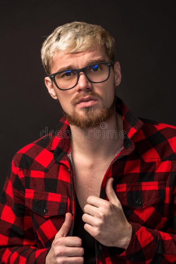 Image of attractive young bearded hipster man wearing glasses dressed in shirt in a cage isolated over black background. stock photo
