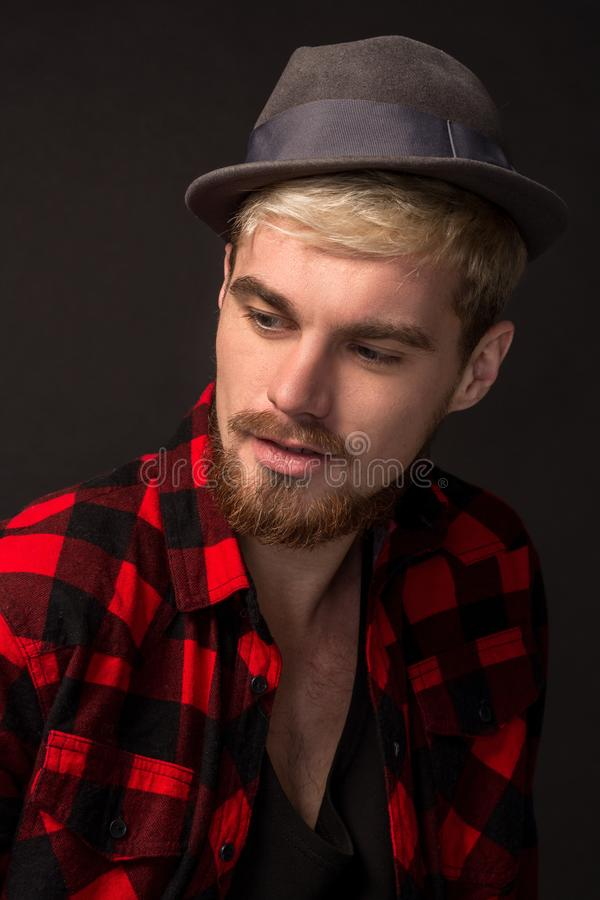 Image of attractive young bearded hipster man wearing hat dressed in shirt in a cage isolated over black background. stock images