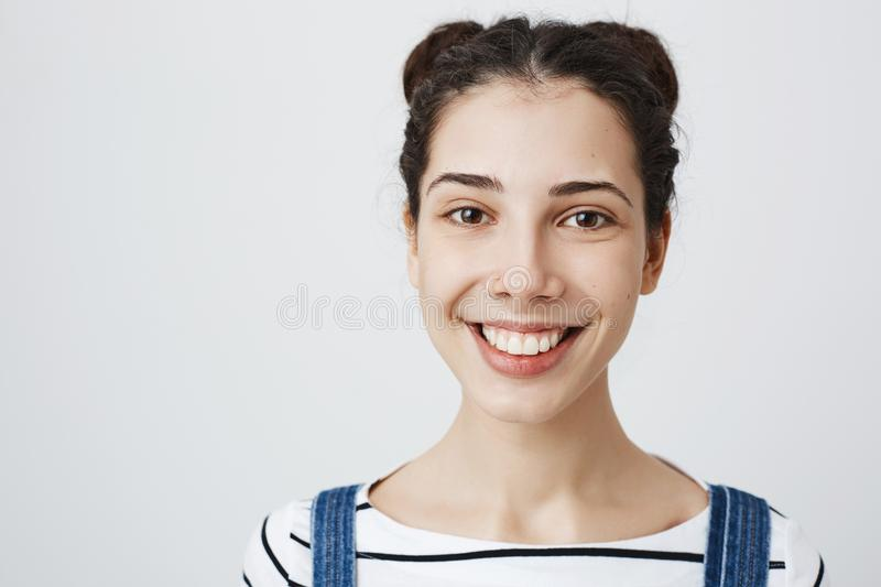 Close-up portrait of attractive young european woman with bright smile, two buns hairstyle and pierced nose, standing. Over gray background. Girl decided to royalty free stock images