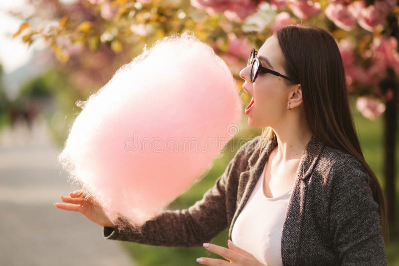 Close up portrait of attractive young girl eating cotton candy in front of pink sakura tree.  royalty free stock photography