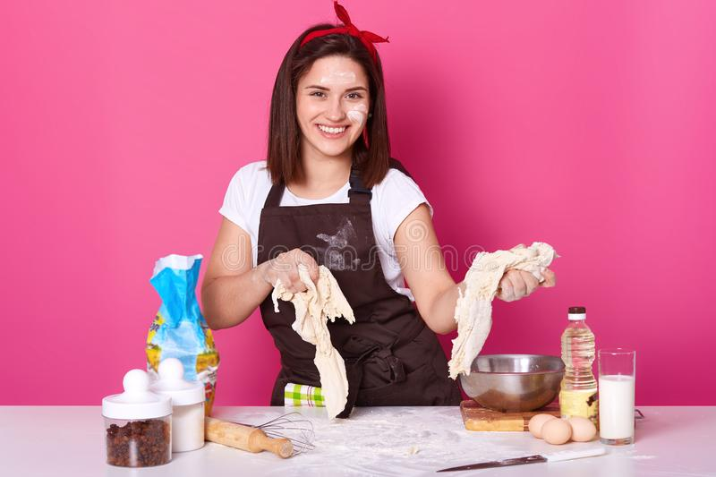 Close up portrait of attractive young girl kneading dough, making bread or pizza, looks smiling directly at camera, wears white t stock image