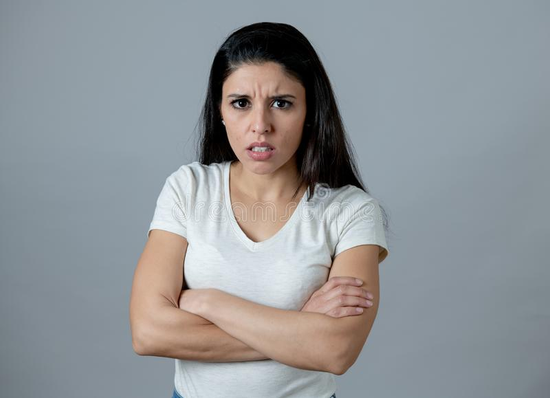 Human expressions and emotions. Young attractive woman with an angry face, looking furious and upset. Close up portrait of an attractive young latin woman with stock image