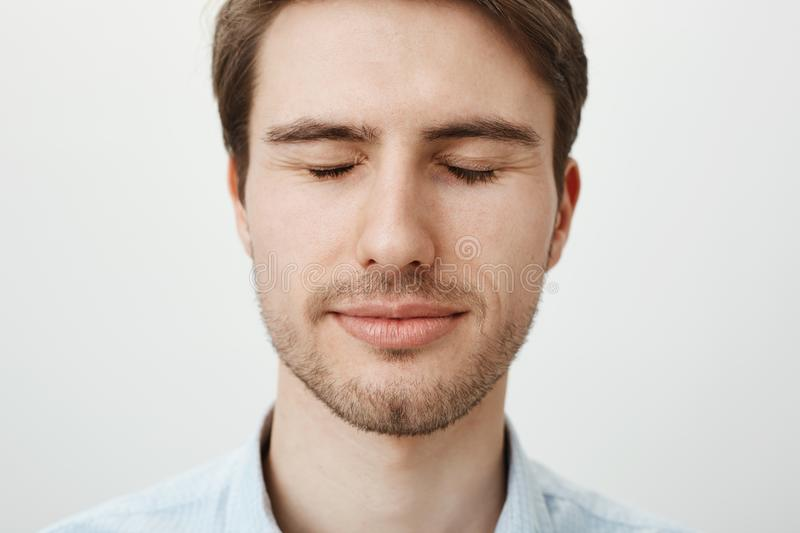 Close-up portrait of attractive young male model with bristle, standing with closed eyes and slight smile, being relaxed. And in good mood while posing against royalty free stock photography