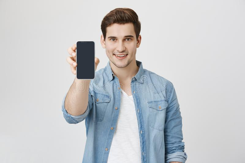 Close up portrait of attractive young model with trendy hairstyle and outfit, presenting new smartphone for advertising. Isolated over white background stock photos