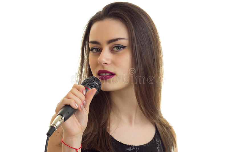 A close-up portrait of attractive young singer with a microphone royalty free stock photos