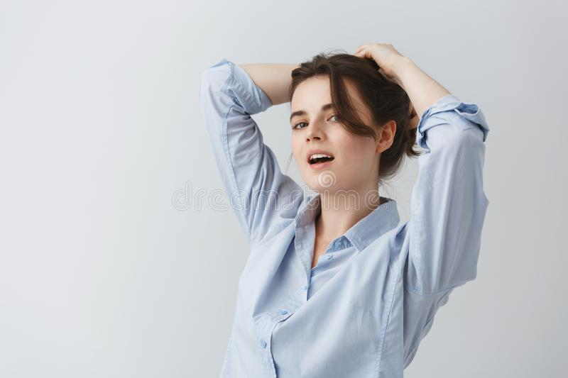 Close up portrait of attractive young woman making herself hairstyle, looking in camera with happy and joyful expression royalty free stock photos