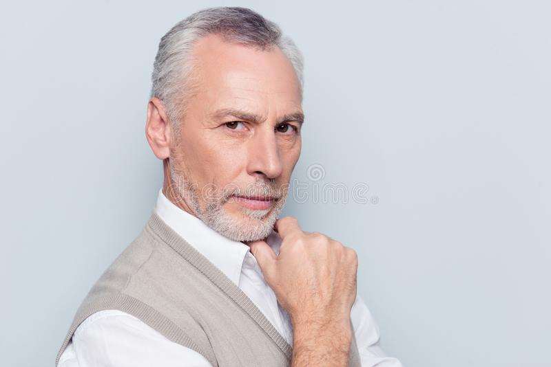 Close up portrait of authoritative clever qualified thoughtful v. Irile masculine old man wearing beige knitted waistcoat white shirt touching chin with hand stock photography