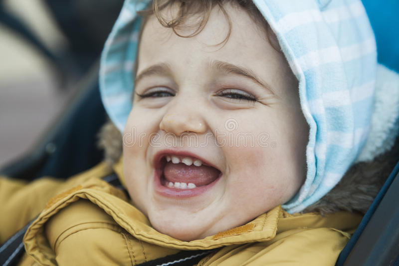 Close up portrait baby boy with big green eyes roar with laughter. Positive emotions stock photo