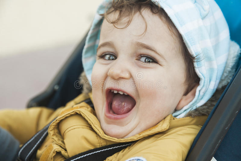 Close up portrait baby boy with big green eyes roar with laughter. Positive emotions royalty free stock images