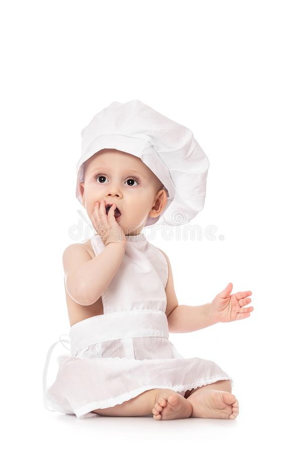 Close up portrait of a baby sitting wearing a chef hat, isolated on white. big size resolution. Food banner for text or design stock images