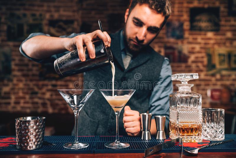 Portrait of barman pouring fancy cocktail in bar at party. Manhattan cocktail beverage in nightclub. Close up Portrait of barman pouring fancy cocktail in bar at stock image