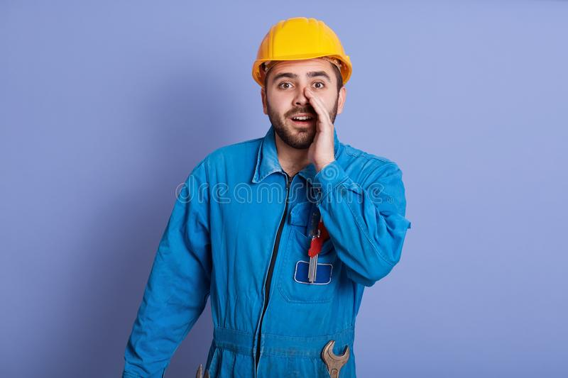 Close up portrait of bearded handsome male constructor yelling something and keeping hands near his opened mouth, foreman wearing stock images