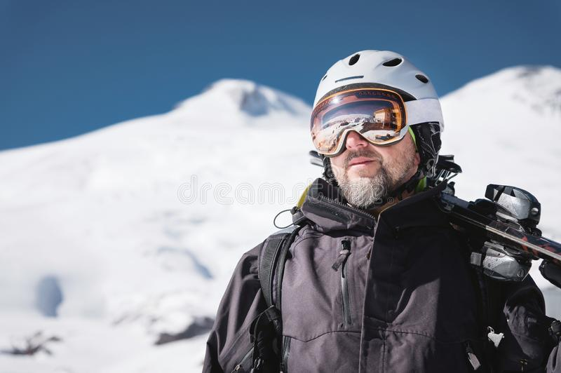 Close-up Portrait bearded male skier aged against background of snow-capped Caucasus mountains. Ski resort concept royalty free stock image