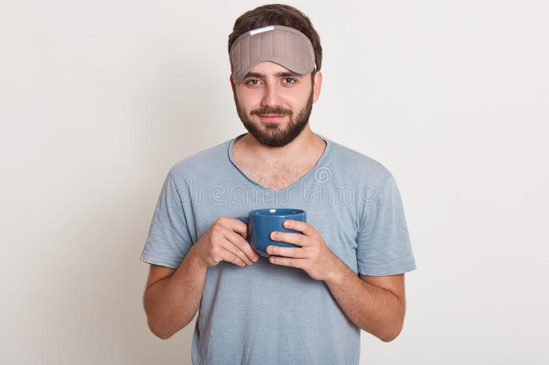 Close up portrait of bearded man in dressing gown and mask to sleep on his head, holding blue mug in his hands, looking directly stock photos