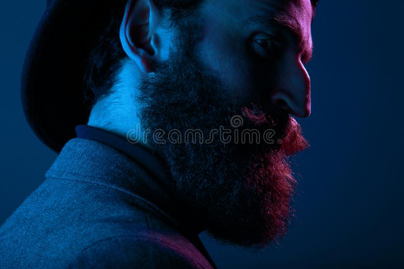 Close up portrait of a bearded man in elegant hat and suit, posing in profile in studio, isolated on blue background. royalty free stock photos