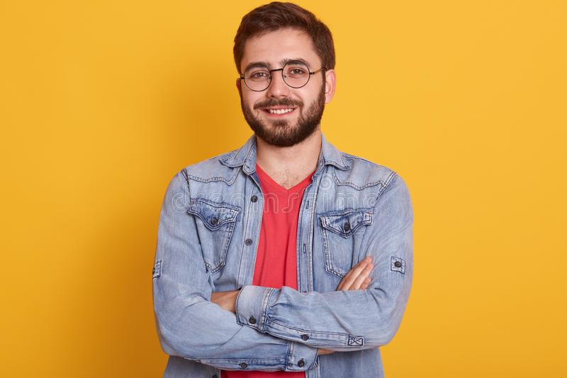 Close up portrait of bearded man with folded hands, sytanding and looking directly at camera with happy facial expression, being royalty free stock image
