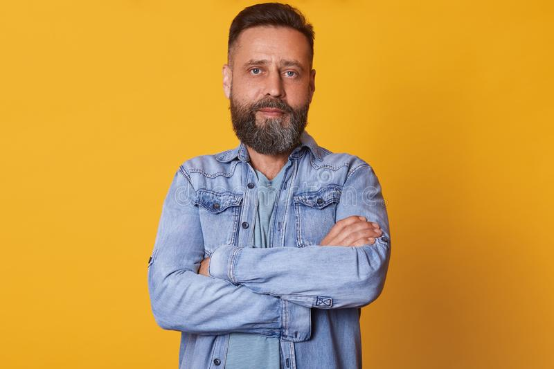 Close up portrait of bearded middle aged confident man with folded arms, standing straight, having serious facial expression,. Wearing casual jeans jacket stock photos