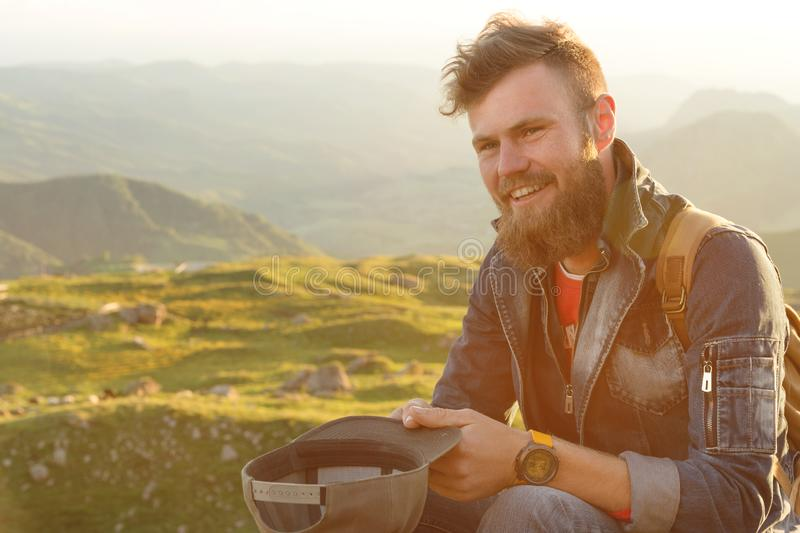 Close-up portrait of a bearded stylish traveler in a cap against epic rocks. Time to travel concept stock photo