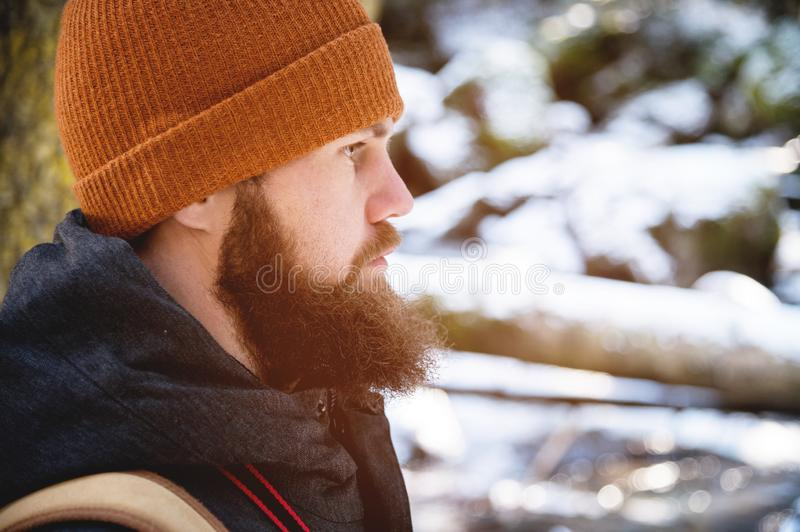 Close-up portrait of a bearded young man in a hat and a backpack in the coniferous forest. The concept of tourism. Side royalty free stock image