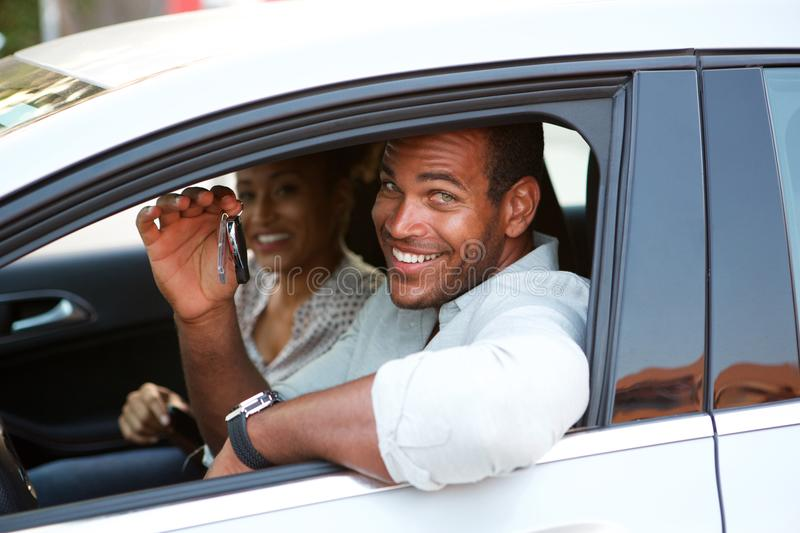 Close up African American couple sitting in car smiling. Close up portrait of beautiful African American couple sitting in car smiling stock photo