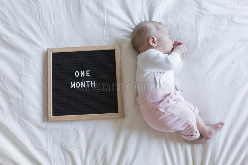 close up portrait of a beautiful baby on white background at home. letter board vintage with one month message royalty free stock photography