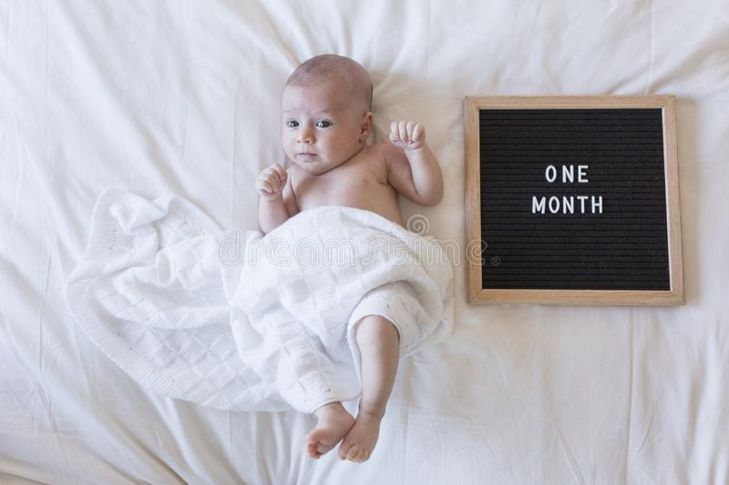 close up portrait of a beautiful baby on white background at home with a vintage letter board with message: one month royalty free stock image