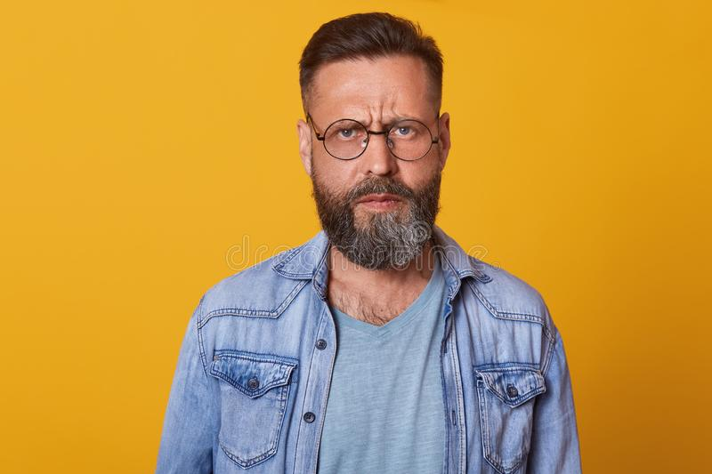 Close up portrait of beautiful bearded guy with stylish hairstyle looks directly at camera with serious and calm facial expression royalty free stock image