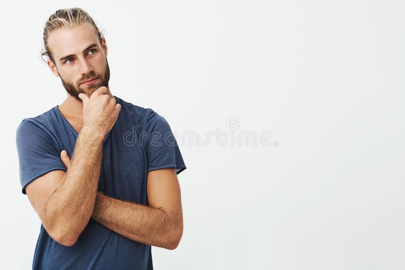 Close up portrait of beautiful bearded man with stylish hairstyle and clothes looking aside and thinking about room stock image
