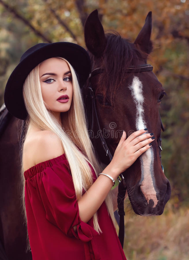 Close-up portrait of a beautiful blonde caucasian girl caressing a horse stock photo