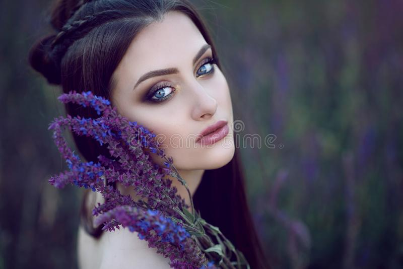 Beautiful blue-eyed lady with perfect make up and plaited hairstyle sitting in the field and holding purple flowers at her face. Close up portrait of beautiful stock photo