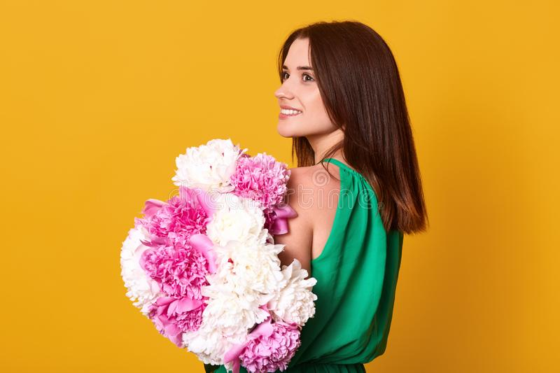 Close up portrait of beautiful brunette girl holds big bouquet with white and rose peonies. Happy stylish woman in green dress. With flowers, charming lady has stock images